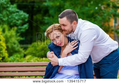 Woman sits on bench, man puts his jacket for girl and hugs she in green park, focus on woman