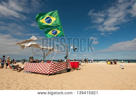 Rio de Janeiro, Brazil - July 18, 2016: Brazilian flags in the wind above tent on a windy day in Copacabana beach.
