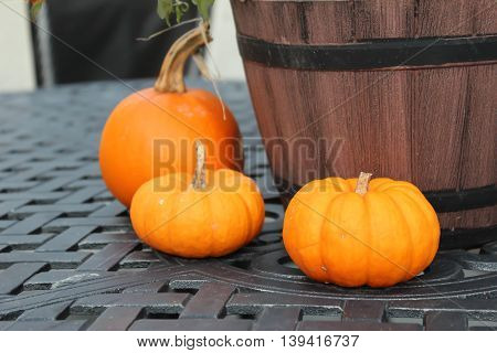 three small pumpkins as fall display on patio table