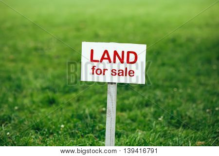 land for sale sign against trimmed lawn background