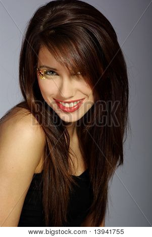 portrait of a beautiful brunette woman wearing black shirt over grey background, fashion shot. beautiful make-up