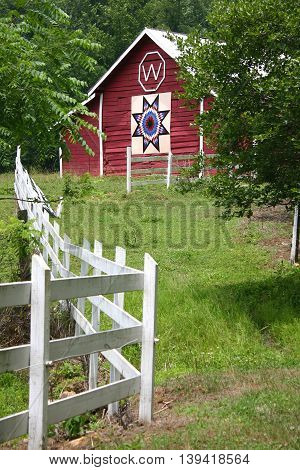 a quilt square on a red barn behind a white fence