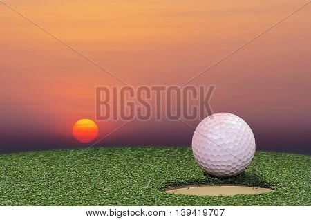 Golf ball on lip of cup with the sunset background.