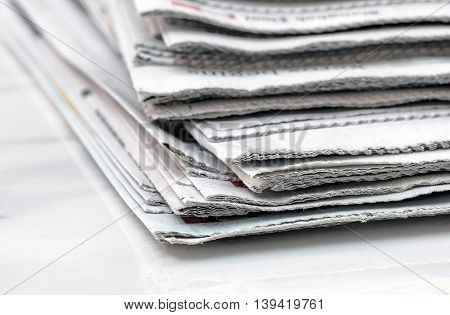 Stack of used newspaper on white table.