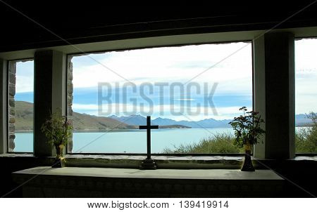 Cross silhouette and a New Zealand lake in background.