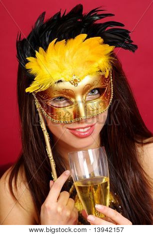 girl in gold carnival mask holding champagne