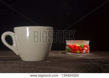 Cup of coffee and a multi-colored pills in a glass jar