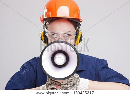 Professions Concepts and Ideas.Portrait of Expressive Caucasian Female With Loudspeaker Horn Shouting In Hardhat. Equipped with Coverall. Horizontal Shot