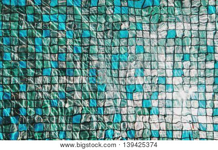 Blue mosaic tiles under swimming pool with rippled water and reflection of bright sunlight