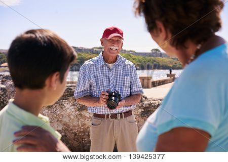 Happy tourists on holidays. Hispanic people traveling in Havana Cuba. Grandfather grandmother and grandchild during summer travel with senior man taking photos with camera