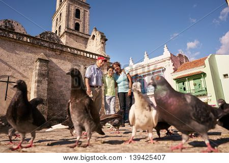 Happy tourists on holiday in Cuba. Hispanic people traveling in Havana. Grandpa and grandson feeding birds giving food to pigeons in square