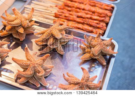 Chinese snackfood starfish on a silver plate outside among other dishes