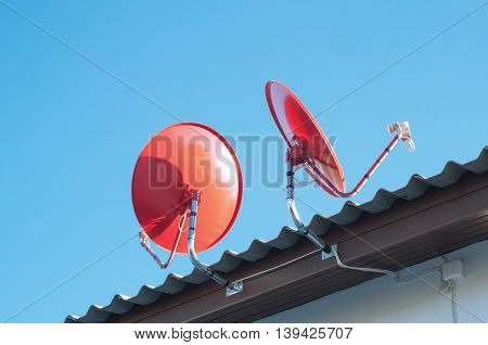 Satellite dish transmission data on background blue sky.