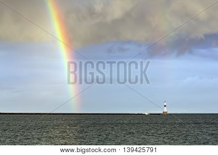 The lighthouse at Conneaut Ohio is graced by a rainbow over Lake Erie.