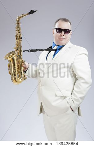 Male Saxo Player in Stylish White Suit and Sunglasses Posing with Lifted Up Saxophone Against White Background. Vertical Image Composition