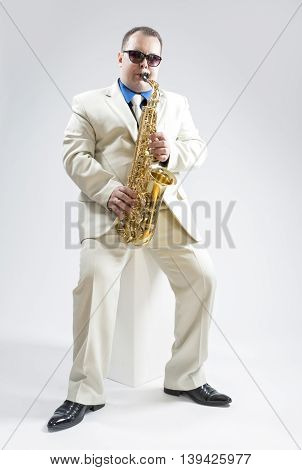Music Concepts and Ideas. Portrait of Hadnsome Male Saxophone Player Performing In Studio Environment. Wearing White Suit and Sunglasses. Vertical Composition