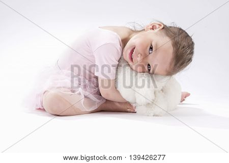 Portrait of Cute Caucasian Female Kid Sitting Together with Plush Toy and Smiling.Horizontral Image Composition