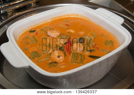 Closeup of a bowl of red thai curry with shrimp and vegetables.