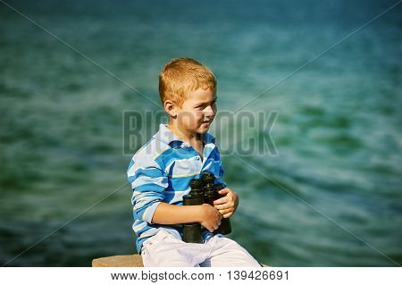 Young boy with binoculars , the sea in the background