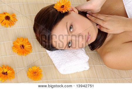 Portrait of frisch und schön brunette Woman Handauflegen Bambusmatte um gelbe Blumen