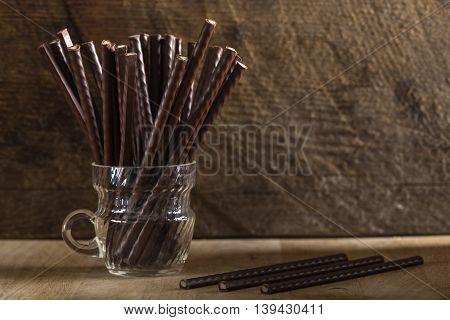 Chocolate sticks filled with mint cream over wooden rustic background