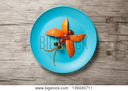 Butterfly made of fruits on plate and wooden background