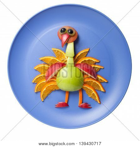 Peacock made of fruits on blue plate