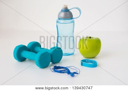 sport, healthy lifestyle and objects concept - close up of dumbbells with fitness tracker, earphones, green apple and water bottle over white background