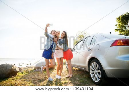 summer vacation, holidays, travel, road trip and people concept - happy teenage girls or young women with smartphone taking selfie near car at seaside