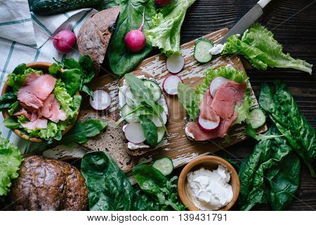 Sandwiches with fresh vegetables, soft cheese and fish on a dark wooden background
