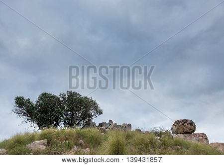 Country scene with hill, grass, rocks and cloudy sky background