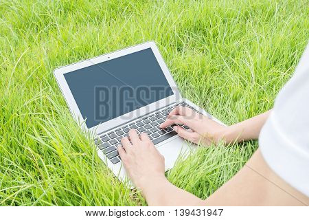 Asian woman lied on grass floor in the garden textured background for use a notebook computer work concept at the outdoor
