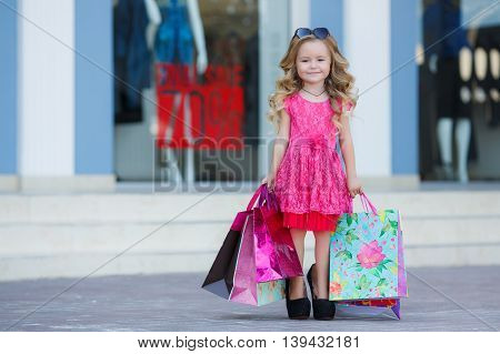 Beautiful little girl with blond long curly hair,sun glasses with glass in the form of hearts,in a pink dress with a bunch of colored shopping bags,posing standing near the entrance to the supermarket
