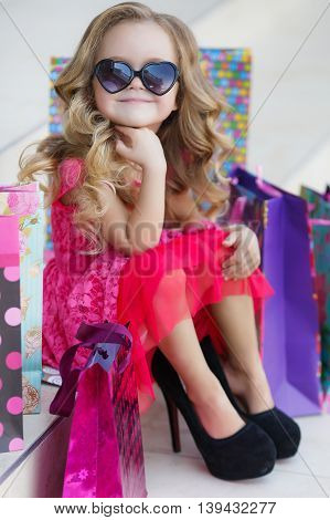 Beautiful little girl with blond long curly hair,sun glasses with glass in the form of hearts,in a pink dress with a bunch of colored shopping bags,posing sitting on the steps near the entrance to the supermarket in a big black mom's shoes