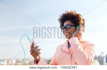 technology, lifestyle and people concept - smiling african american young woman or teenage girl with smartphone and headphones listening to music outdoors