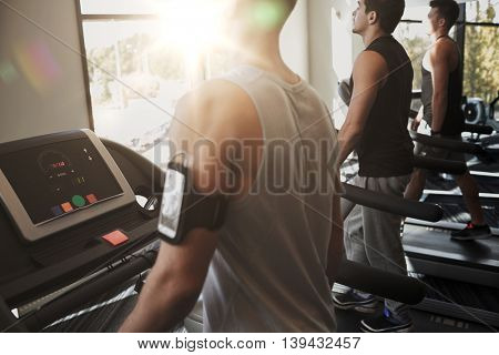 sport, fitness, lifestyle, technology and people concept - smiling men exercising on treadmill in gym