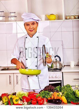 Happy man professional in chef hat cooking chicken. Cooking chiken with vegetable. Man cooking at kitchen.