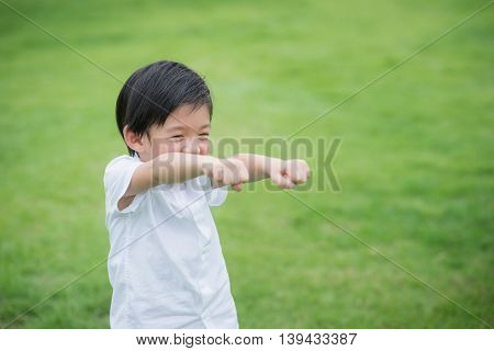 Cute Asian child playing on green grass
