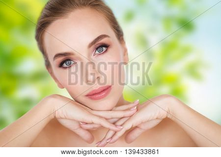 beauty, people, eco and bodycare concept -beautiful young woman face and hands over green natural background