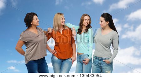 friendship, fashion, body positive, diverse and people concept - group of happy different size women in casual clothes over blue sky and clouds background