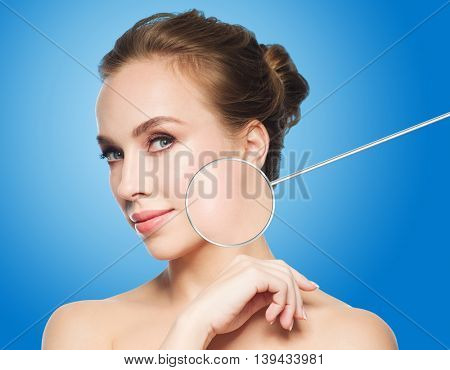 beauty, people and skin care concept - beautiful young woman face and circle with magnified smooth facial skin area over blue background