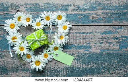 Daisy flowers in heart shape with gift box and tag on blue painted wooden board