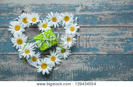 Daisy flowers in heart shape with a gift box on blue painted wooden board