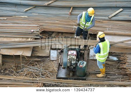 SELANGOR, MALAYSIA -JULY 05, 2016: Construction workers working at the reinforcement bar bending yard in the construction site.