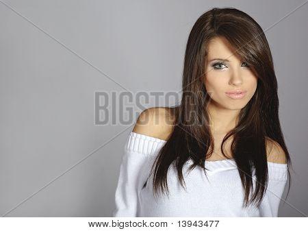 Porträt einer schönen sexy Frau gegenüber dem grauen Hintergrund