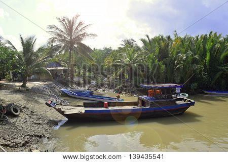 boat anchor on river bank with vietnamese rural house