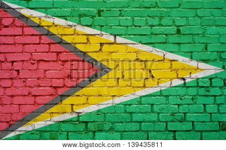 Flag of Guyana painted on brick wall background texture
