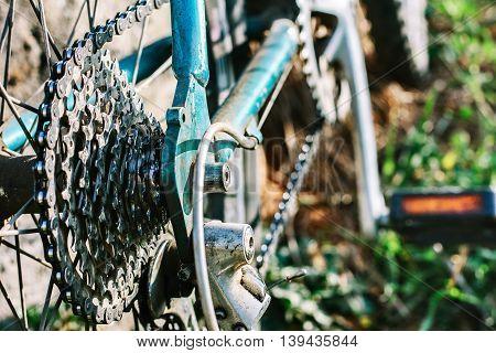 Macro of blue metal bike part and chain.Bokeh