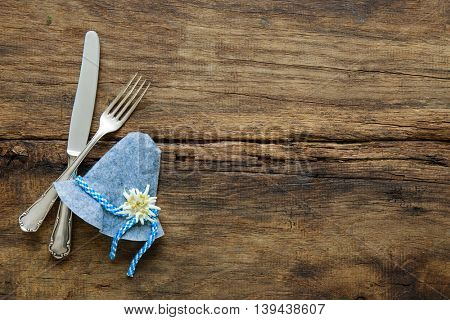 Cutlery and Bavarian hut with edelweiss on wooden table with copy space for Oktoberfest