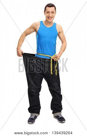 Full length portrait of a young guy in oversize jeans measuring his waist isolated on white background